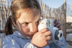 Nettes kleines glückliches Mädchen mit Sofortbildfotokamera Lizenzfreies Stockfoto