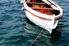 Nettes kleines hölzernes weißes Boot auf einem blauen Meer stockfotografie