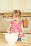 Nettes kleines Helfermädchen, das ihrer Mutter kocht in einer Küche hilft Glückliche liebevolle Familie bereiten Bäckerei vor Stockfotografie