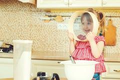 Nettes kleines Helfermädchen, das ihrer Mutter kocht in einer Küche hilft Glückliche liebevolle Familie bereiten Bäckerei vor Stockfotos
