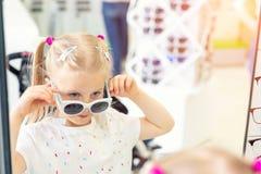 Nettes kleines junges kaukasisches blondes M?dchen, das an versucht und Sonnenbrille vor Spiegel am Optikeyewearspeicher w?hlt ad lizenzfreie stockfotografie