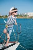 Nettes kleines Kapitänkindertragender Kapitänhut und modische Sonnenbrille, die in den Abstand steht an Bord des Luxusbootes blic Stockbild