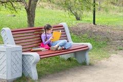 Nettes kleines kaukasisches Mädchenlesebuch, das auf einer Bank sitzt Stockbilder