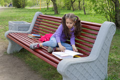 Nettes kleines kaukasisches Mädchenlesebuch, das auf einer Bank sitzt Lizenzfreie Stockfotografie