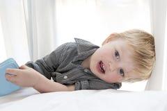 Nettes kleines Kind, das auf Bett mit Buch liegt Lizenzfreie Stockfotografie