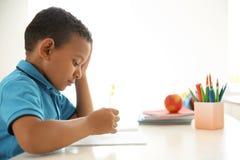 Nettes kleines Kind, das Aufgabe am Schreibtisch im Klassenzimmer tut stockfotos