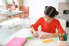 Nettes kleines Kind, das Aufgabe am Schreibtisch im Klassenzimmer tut lizenzfreie stockfotos