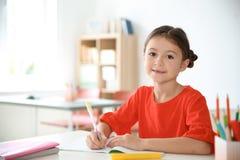 Nettes kleines Kind, das Aufgabe am Schreibtisch im Klassenzimmer tut stockfotografie