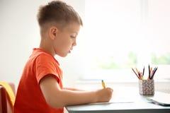 Nettes kleines Kind, das Aufgabe am Schreibtisch im Klassenzimmer tut lizenzfreie stockbilder