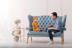 Nettes kleines Kind, das gegenüber von ihrem Vater sitzt Stockfotografie