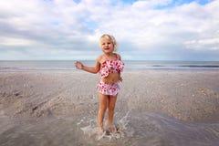 Nettes kleines Kind, das im Wasser auf dem Strand durch den Ozean spritzt und spielt stockbild