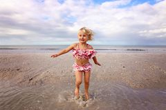 Nettes kleines Kind, das im Wasser auf dem Strand durch den Ozean spritzt und spielt stockfotografie