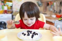 Nettes kleines Kind isst Quark mit Beere Stockfotografie