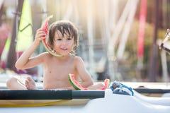 Nettes kleines Kind, Junge, Wassermelone auf dem Strand essend Stockfoto