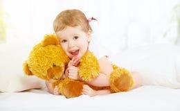 Nettes kleines Kindermädchen, das Teddybären im Bett umarmt Lizenzfreie Stockfotografie