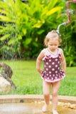 Nettes kleines Kindermädchen im Badeanzug, der in der Dusche auf tropischem Erholungsort badet Stockfoto