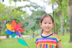Nettes kleines Kindermädchen mit Windkraftanlage im Garten stockfoto