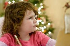 Nettes kleines Kindermädchen schreibt Santa Claus den Brief nahe Weihnachtsbaum zuhause Stockfotos