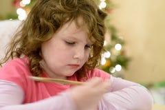 Nettes kleines Kindermädchen schreibt Santa Claus den Brief nahe Weihnachtsbaum zuhause Lizenzfreies Stockbild