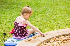 Nettes kleines Kindermädchen in einem Badeanzug, der mit Steinen auf einem Pebble Beach spielt Stockfotografie