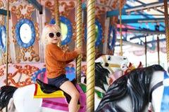 Nettes kleines Kleinkind-Mädchen in der großen Sonnenbrille, die auf Karneval Ca fährt lizenzfreies stockbild