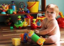 Nettes kleines Kleinkind mit dem Ingwerhaar, das auf dem Boden unter sitzt Lizenzfreie Stockfotos