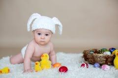 Nettes kleines Kleinkindbaby, spielend mit bunten Ostereiern stockbilder