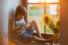 Nettes kleines Kleinkindkind, spielend mit Abakus auf einem Fenster Stockbilder