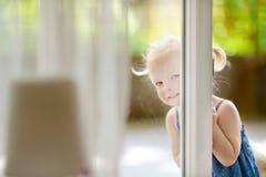 Nettes kleines Kleinkindmädchen, das in ein Fenster späht Stockfotografie