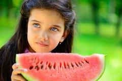Nettes kleines lateinisches Mädchen, das Wassermelone isst Stockbilder