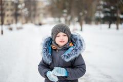 Nettes kleines lustiges Kind in der bunten Winterkleidung, die Spaß mit Schnee, draußen während der Schneefälle hat Des Active Fr Lizenzfreies Stockbild