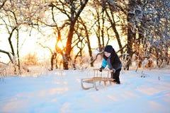 Nettes kleines lustiges Kind in der Winterkleidung, die Spaß mit Schnee, draußen während der Schneefälle hat Aktive Freizeitkinde Stockfotos