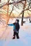Nettes kleines lustiges Kind in der Winterkleidung, die Spaß mit Schnee, draußen während der Schneefälle hat Aktive Freizeitkinde Lizenzfreie Stockfotos