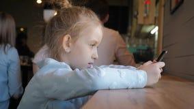 Nettes kleines Mädchen, das am intelligenten Telefon am Café verwendet Glückliches Kind, das den Spaß und Entspannung nach der Sc stock video footage