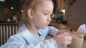 Nettes kleines Mädchen, das am intelligenten Telefon am Café verwendet Glückliches Kind, das den Spaß und Entspannung nach der Sc stock footage