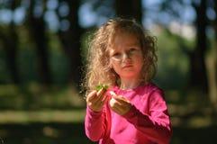 Nettes kleines Mädchen überprüft sorgfältig das grüne Blatt, ernsten Blick, gelocktes Haar, sonniges Sommerporträt Stockfotografie