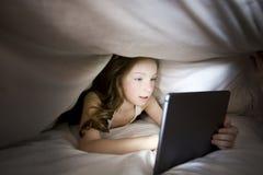 Nettes kleines Mädchen allein mit Tablet-Computer unter Decke nachts in einer Dunkelkammer stockfoto