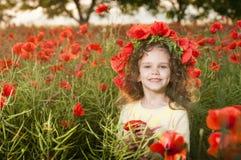 Nettes kleines Mädchen auf dem Mohnblumegebiet Stockfotografie