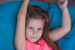 Nettes kleines Mädchen auf den Bohnentaschen, stehend, Porträt, langes Haar still Stockfoto
