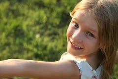 Nettes kleines Mädchen auf der Wiese am Sommertag Lizenzfreies Stockbild