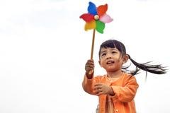 Nettes kleines Mädchen auf Gras am Sommertag hält Windmühle Stockbild