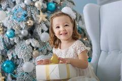 Nettes kleines Mädchen in bklom Kleid, das in einem Stuhl sitzt und öffnet Kasten mit Geschenk für Hintergrund Weihnachtsbaumblau lizenzfreie stockfotos