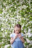 Nettes kleines Mädchen in blühendem Apfelbaumgarten am Frühling Lizenzfreies Stockbild