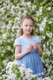 Nettes kleines Mädchen in blühendem Apfelbaumgarten am Frühling Lizenzfreies Stockfoto