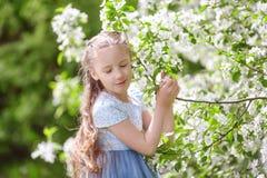 Nettes kleines Mädchen in blühendem Apfelbaumgarten am Frühling Lizenzfreie Stockfotos