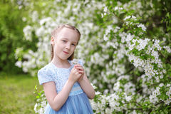 Nettes kleines Mädchen in blühendem Apfelbaumgarten am Frühling Lizenzfreie Stockbilder