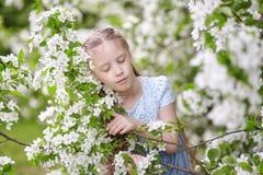 Nettes kleines Mädchen in blühendem Apfelbaumgarten am Frühling Lizenzfreie Stockfotografie