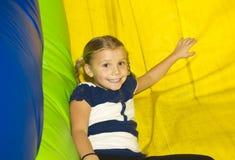 Nettes kleines Mädchen, das auf aufblasbarer Seite spielt Lizenzfreies Stockfoto