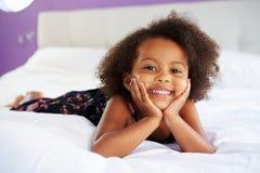 Nettes kleines Mädchen, das auf Bauch im Bett des Elternteils liegt Lizenzfreie Stockbilder