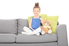 Nettes kleines Mädchen, das auf Couch mit Teddybären sitzt Stockbild
